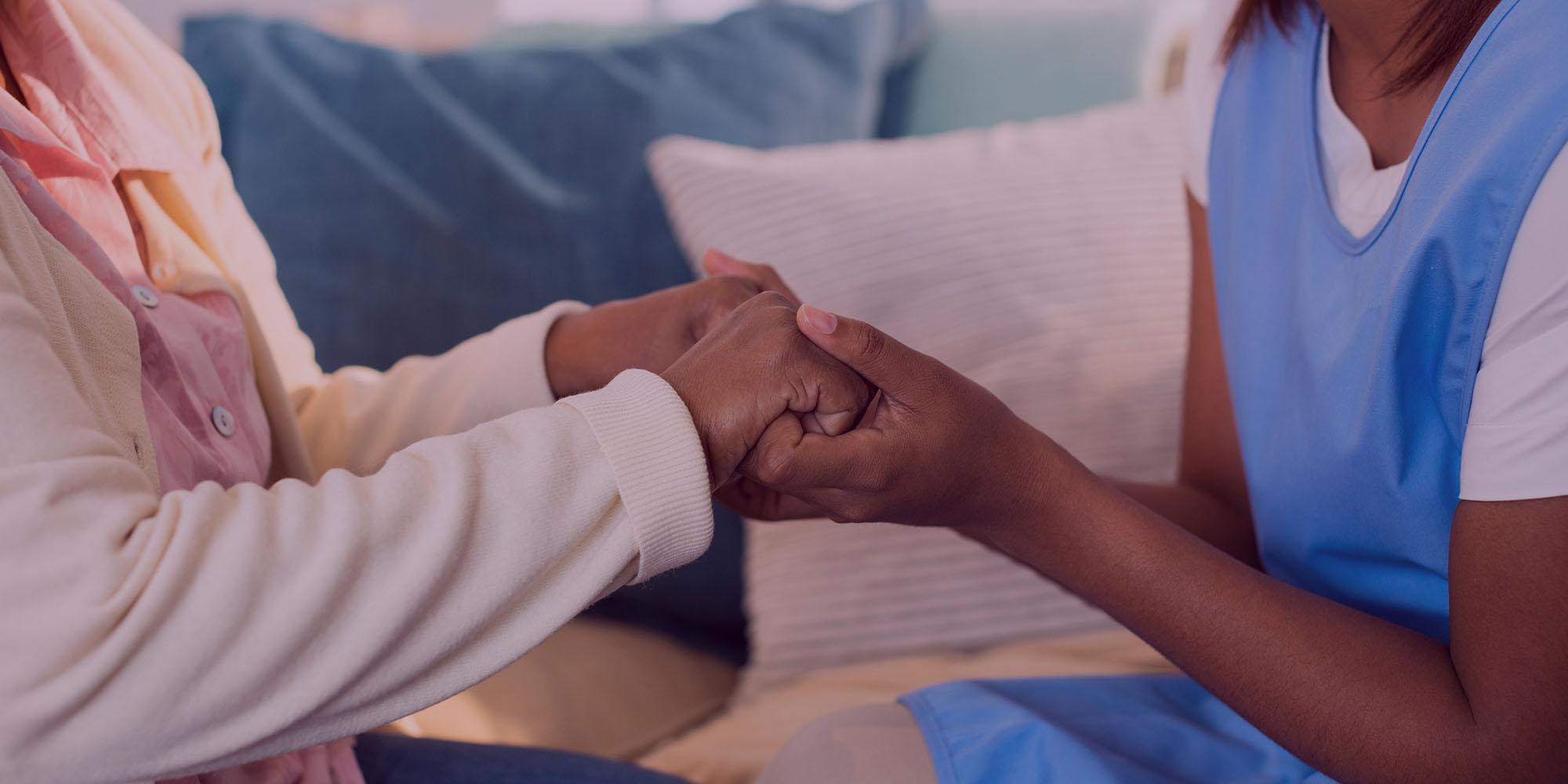 Personnel d'aide à domicile se tenant la main avec un client âgé